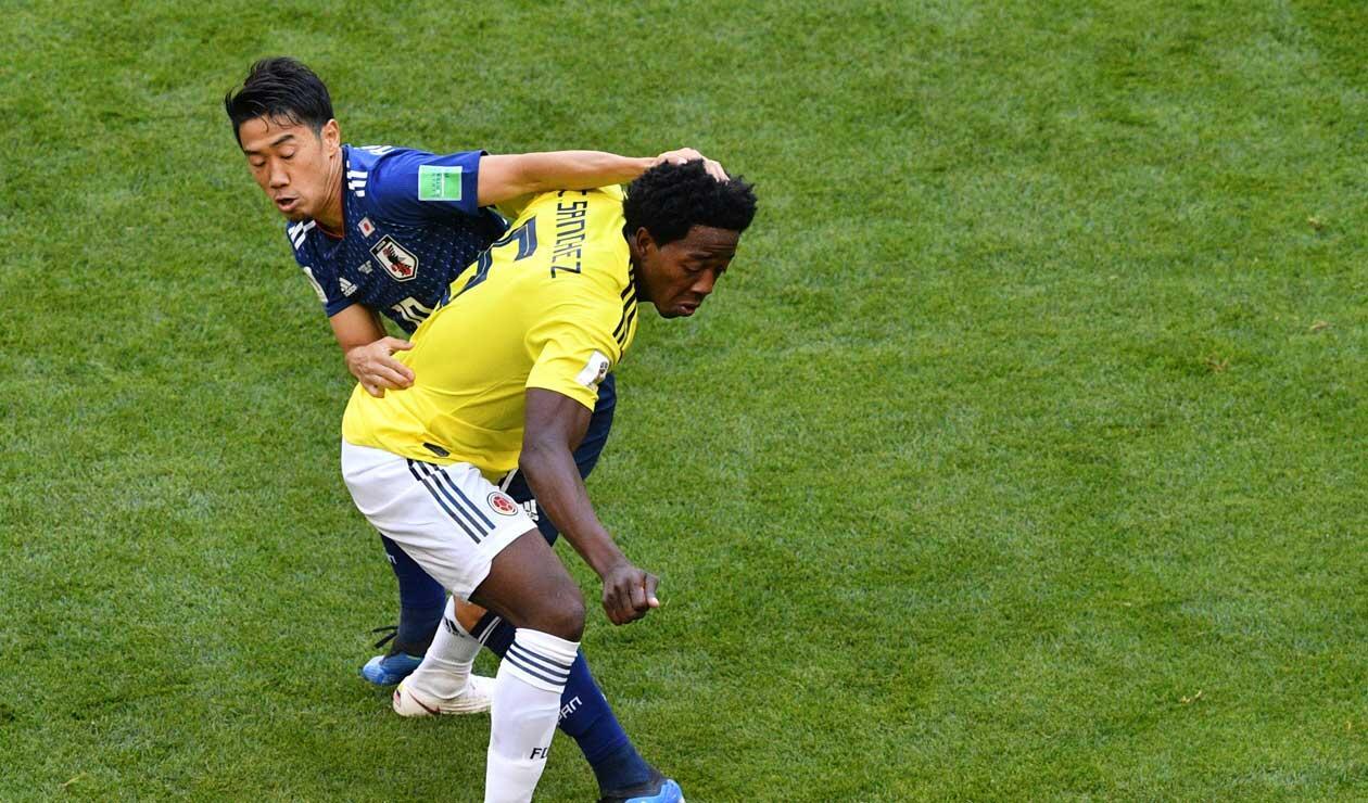 Carlos Sánchez disputando una pelota con su similar de Japón