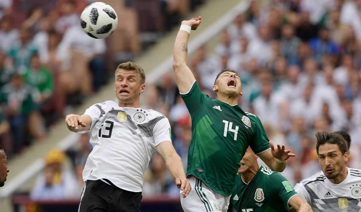 El alemán Thomas Müller disputa un balón con Javier Hernández de México
