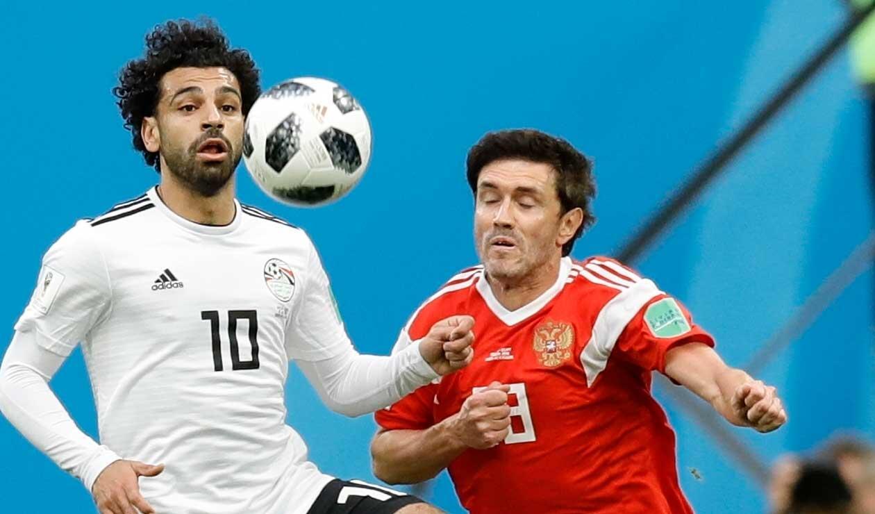 El egipcio Mohamed Salah defiende un balón con Yuri Shirkov de Rusia