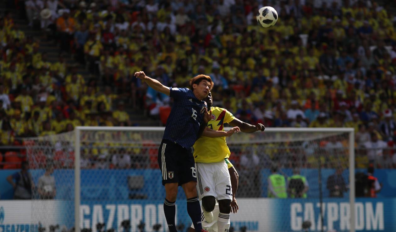 Pelota dividida entre un jugador colombiano y otro japonés durante la primera mitad