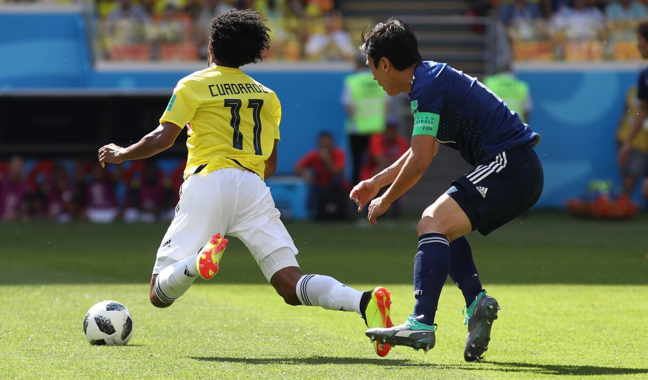 Cuadrado recibiendo una falta de un futbolista japonés