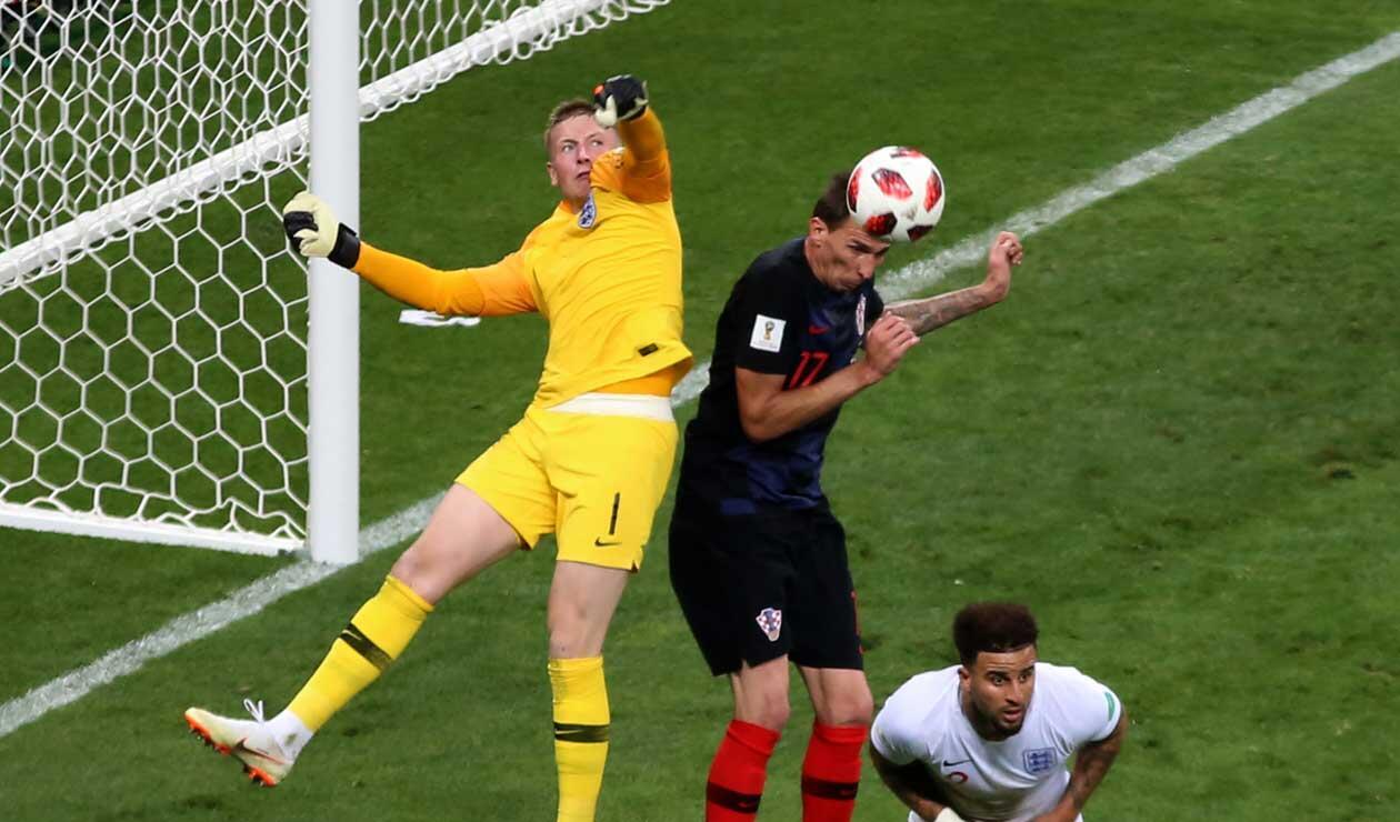 Jordan Pickford intenta rechazar un balón ante la insistencia de Mario Mandzukic