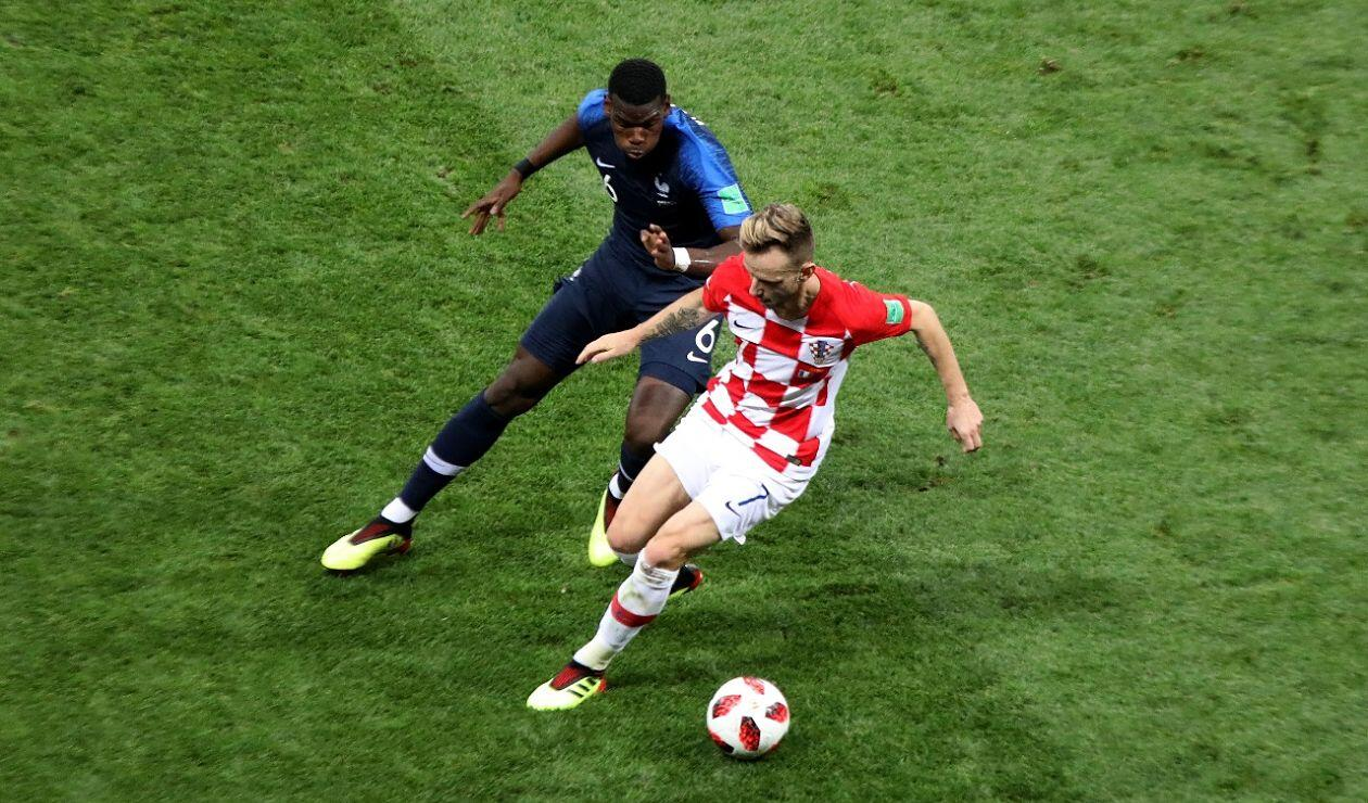 Ivan Rakitić defiende una pelota pretendida por Paul Pogba