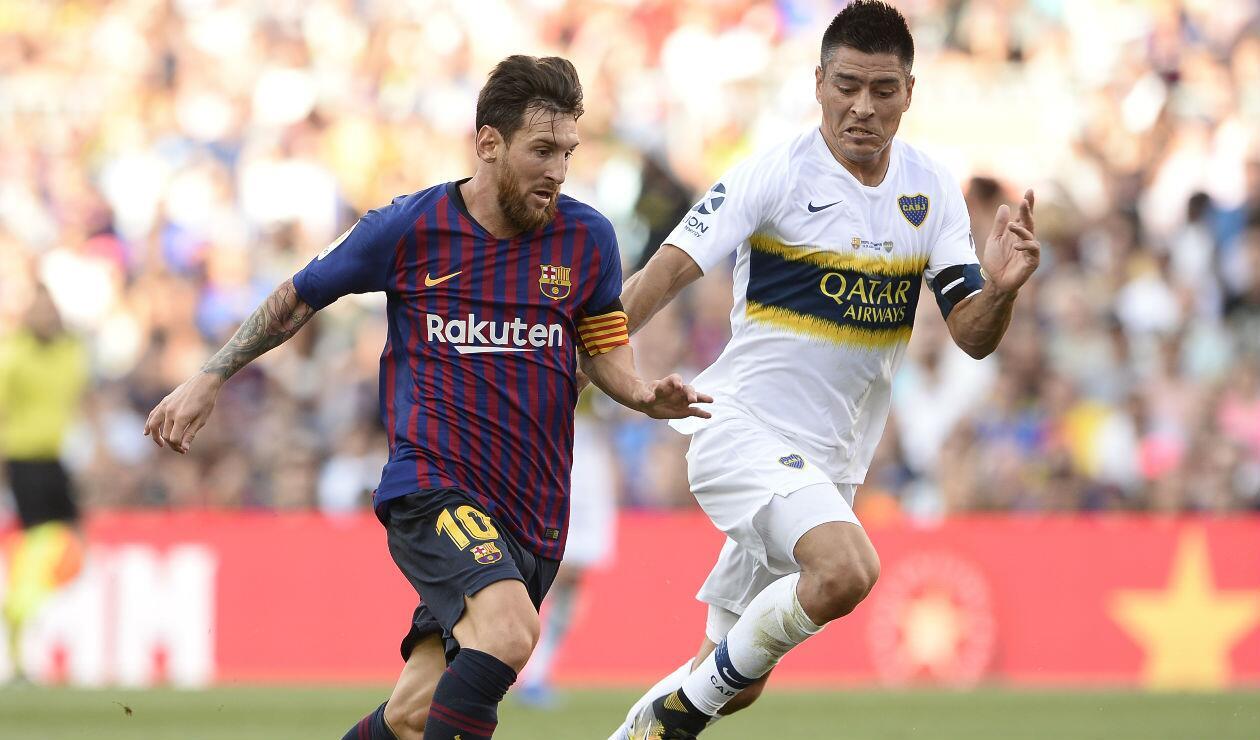 Lionel Messi del Barcelona disputa un balón con Paolo Goltz de Boca Juniors