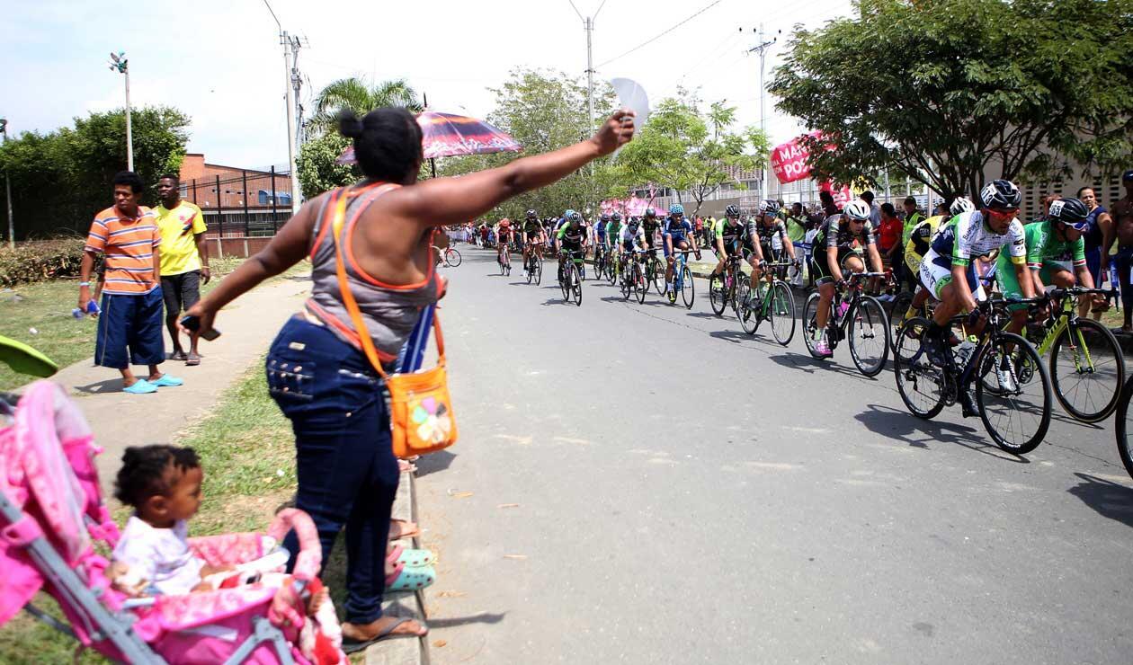 Los aficionados alientan a los corredores en el Clásico RCN en las calles del distrito de Agua Blanca