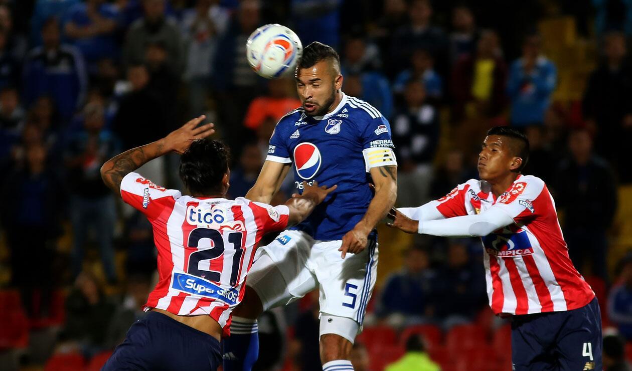 Andrés Cadavid (Millonarios) intenta cabecear un balón ante el acecho de los jugadores del Junior