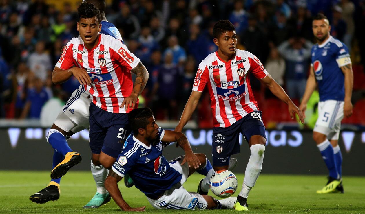 César Carrillo (Millonarios) es derribado ante la presión de dos jugadores del Junior