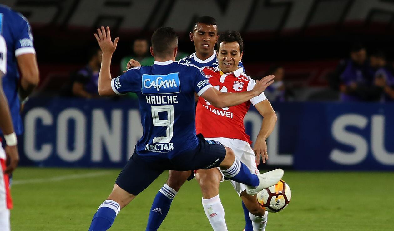Diego Güastavino (Santa Fe) ante la marca de dos jugadores de Millonarios