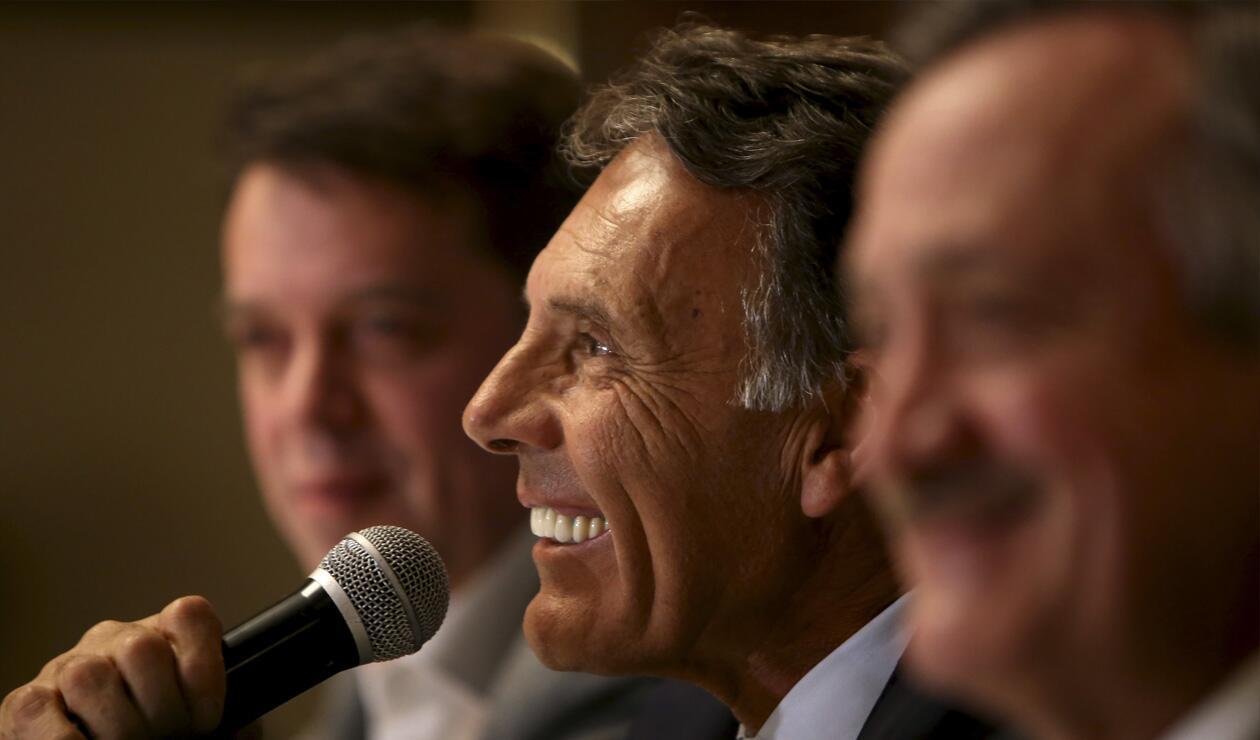 Miguel Russo en medio de Gustavo Serpa, máximo accionista, y Enrique Camacho, presidente de Millonarios