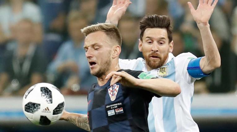 Rakitic disputan un balón con Lionel Messi