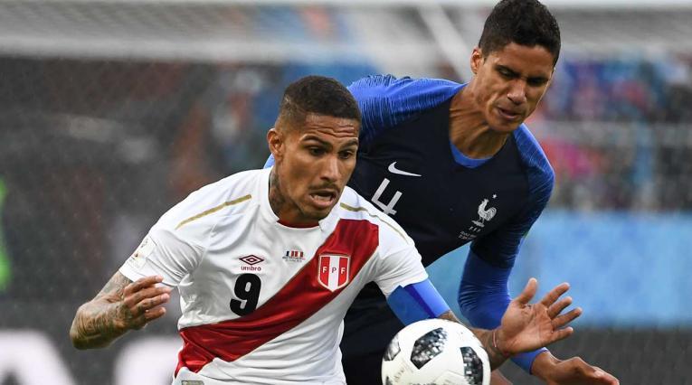 El peruano Paolo Guerrero defiende el balón ante el acoso del francés Raphael Varane