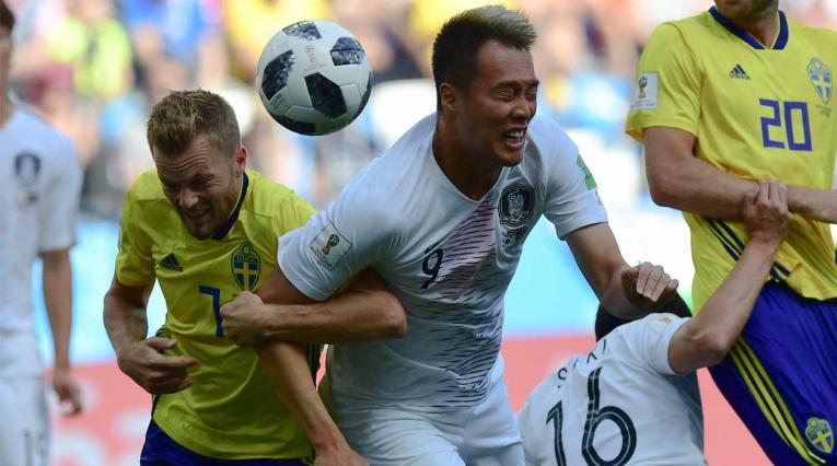 El sueco Sebastian Larsson (C-L) y Kim Shin-wook de Corea del Sur disputan un balón