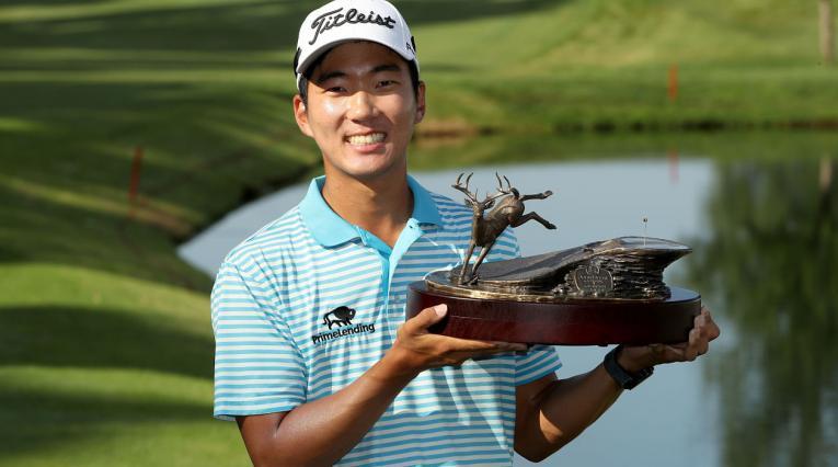 Michael Kim posa con el trofeo después de ganar el John Deere Classic