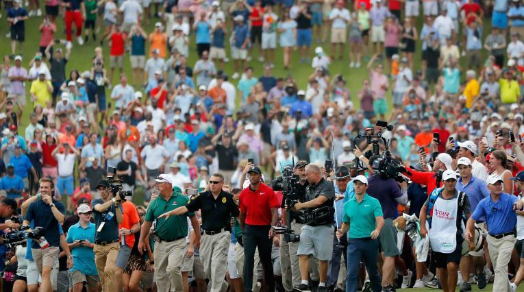 Tiger Woods y Rory Macilroy caminan con una orda de aficionados detrás suyo.