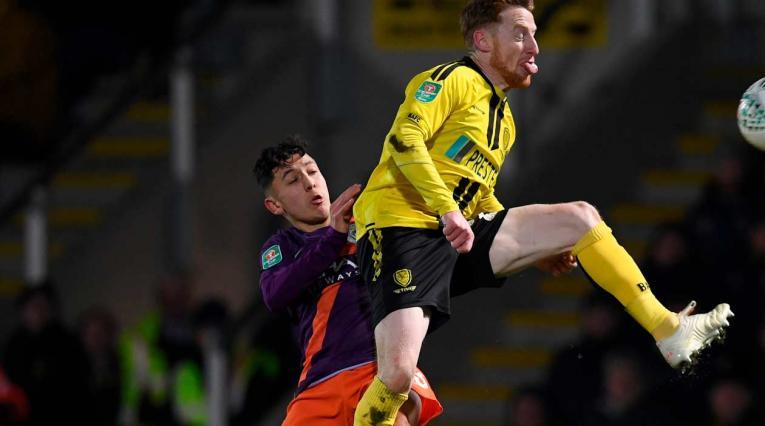 Ian Carlo Poveda lucha por el balón con un jugador del Burton Albion